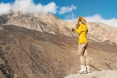Фотограф девушки в солнечных очках и большой меховой шапке и желтом цвете связал стойки свитера на фоне максимума Стоковые Фотографии RF