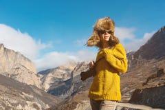 Фотограф девушки в солнечных очках и большой меховой шапке и желтом цвете связал стойки свитера на фоне максимума Стоковые Изображения