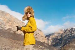 Фотограф девушки в солнечных очках и большой меховой шапке и желтом цвете связал стойки свитера на фоне максимума Стоковое Фото