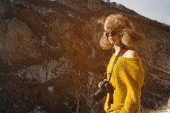 Фотограф девушки в солнечных очках и большой меховой шапке и желтом цвете связал стойки свитера на фоне максимума Стоковые Фото