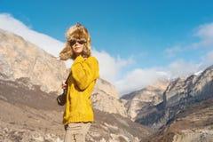 Фотограф девушки в солнечных очках и большой меховой шапке и желтом цвете связал стойки свитера на фоне максимума Стоковые Изображения RF