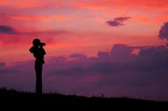 Фотограф девушки на заходе солнца Стоковое Фото