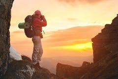 Фотограф девушки с рюкзаком в горах фотографируя заход солнца Стоковое Изображение