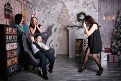 Фотограф девушки фотографируя семью в праздничном интерьере Стоковые Фото