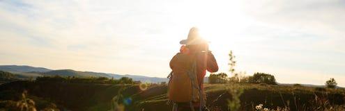 Фотограф женщины принимая фото на верхней части горы захода солнца Стоковое фото RF