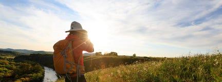 Фотограф женщины принимая фото на верхней части горы захода солнца Стоковые Фотографии RF