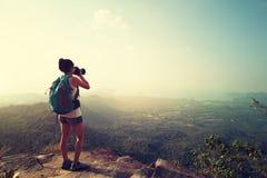 Фотограф женщины принимая фото на горный пик стоковые изображения