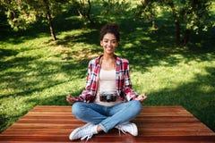 Фотограф женщины сидя outdoors в парке размышляет Стоковые Фото