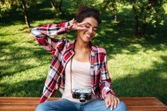 Фотограф женщины сидя outdoors в парке Стоковое Фото