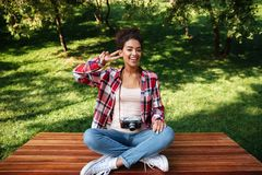 Фотограф женщины сидя outdoors в парке Стоковые Фотографии RF