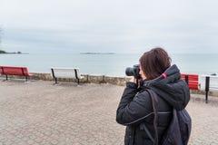 Фотограф женщины фотографируя внешние Стоковая Фотография