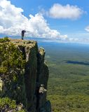 Фотограф живой природы на саммите горы фотографируя заход солнца в ландшафте и голубом небе стоковое изображение