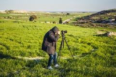 Фотограф или путешественник используя профессиональную камеру DSLR на треноге в природе для предпосылки Стоковая Фотография RF