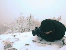 Фотограф кладет в снег и фото принимать замороженной травы с камерой зеркала на шею Стоковые Изображения