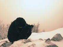 Фотограф кладет в снег и фото принимать замороженной травы с камерой зеркала на шею Стоковая Фотография RF