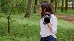 Фотограф молодой женщины работая отростчатый снимать outdoors в природе парка видеоматериал