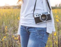 Фотограф молодой женщины с ретро камерой в цветочном саде, wa Стоковые Изображения