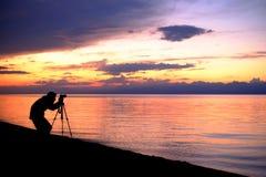 Фотограф на фоне захода солнца моря Стоковое Изображение RF