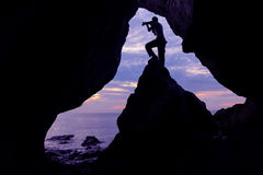 Фотограф перед пещерой около моря Стоковое Изображение
