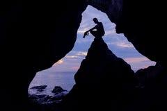 Фотограф перед пещерой около моря Стоковые Изображения RF