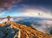 Фотограф принимает заход солнца в горах стоковые изображения rf