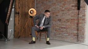 Фотограф принимает фото бизнесмена в студии акции видеоматериалы