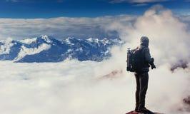Фотограф природы на скале принимает фото с пиком камеры зеркала утеса Стоковые Фотографии RF