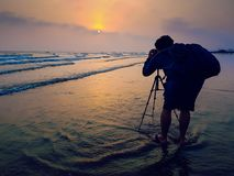 Фотограф при bagpack принимая фото восхода солнца на bea стоковая фотография