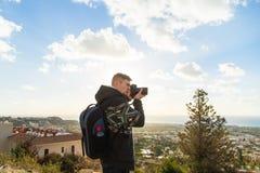 Фотограф путешественника с цифровой фотокамера na górze горы Стоковые Фото