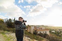 Фотограф путешественника с цифровой фотокамера na górze горы Стоковое Фото