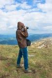 Фотограф снимает ландшафты на верхней части горы Стоковое Изображение