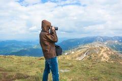 Фотограф снимает ландшафты на верхней части горы Стоковая Фотография