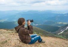 Фотограф снимает ландшафты на верхней части горы Стоковые Изображения