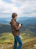 Фотограф снимает ландшафты на верхней части горы Стоковое Изображение RF