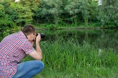 Фотограф снимает на предпосылке реки Стоковое Изображение RF