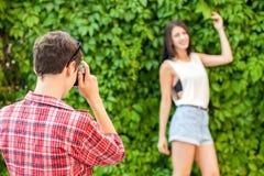 Фотограф снимая красивую модель брюнет около зеленой стены Стоковые Изображения