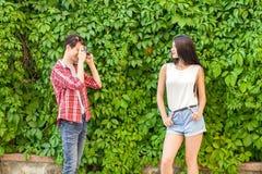 Фотограф снимая красивую модель брюнет около зеленой стены Стоковые Фотографии RF