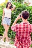 Фотограф снимая красивую модель брюнет около зеленой стены Стоковая Фотография