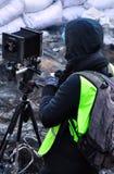 Фотограф стоя около старой камеры на предпосылке баррикад стоковые фото