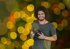 фотограф с камерой на руках Зеленая желтая и красный цвет сдерживают предпосылку и перекрытие bokeh Стоковое Фото