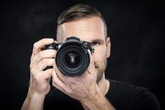 Фотограф с камерой на черноте Стоковые Изображения