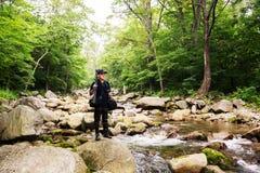Фотограф с камерой путешествует через реку горы стоковая фотография