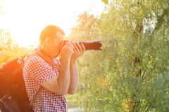 Фотограф с камерой SLR и рюкзак в природе, взгляде со стороны Стоковая Фотография RF