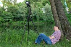 Фотограф уснувший пока снимающ на фоне реки Стоковые Изображения