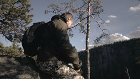 Фотограф фотографирует ландшафт от гор и реки на заходе солнца человек стоит на холме и акции видеоматериалы
