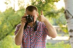 Фотограф фотографирует на фоне растительности Вид спереди большие пальцы руки вверх Стоковое Фото