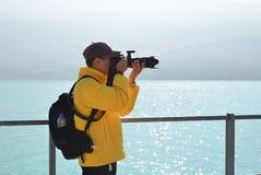 Фотограф фотографируя около озера стоковое изображение rf