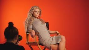 Фотограф фотографируя blondy сексуальная модель девушки в студии Стоковое Изображение RF