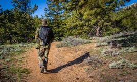 Фотограф человека в обмундировании камуфлирования открывая природу в лесе с камерой фото DSLR, объективами, треногой в задней час Стоковые Фотографии RF