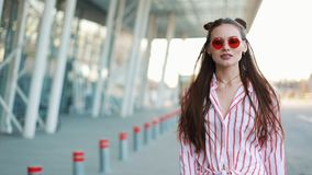 Фотомодель в красных солнечных очках идет уверенно вдоль улицы около торгового центра взрослые молодые сток-видео